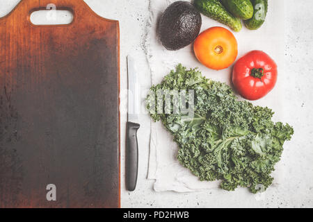 Ingredients for a healthy salad on a white table, top view. Cooking of vegetable salad from tomatoes, cucumbers, avocado and kale. Healthy vegan food  - Stock Photo
