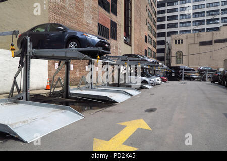 Owing to lack of space some car parks in Manhattan, New York stack cars as a method of parking vehicles - Stock Photo