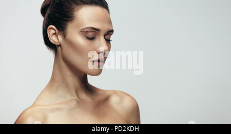 Close up portrait of attractive young woman with dotted line under eyebrow. Female model under going facial plastic surgery. - Stock Photo