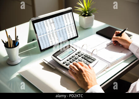 Close-up of a businessman's hand calculating invoice using calculator - Stock Photo