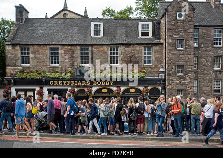 A walking tour stops at Greyfriars Bobby statue and public house, blocking the pavement and forcing pedestrians to walk on the road. - Stock Photo