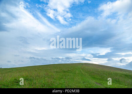 Green grass hills landscape in summer against blue sky and beautiful white clouds. Minimal nature background. - Stock Photo