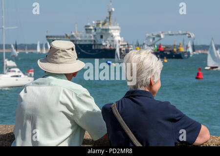 an elderly or older couple man and woman watching the yacht races and competition at cowes week on the isle of wight. trinity house ship galatea - Stock Photo