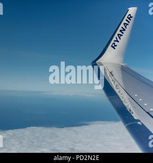 Ryanair, budget airline, Boeing 737 airplane flying in the blue sky. Wing with logo on winglet. Copy space. - Stock Photo