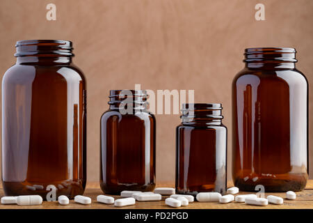 Four pharmaceutical bottles with different pills and capsules - Stock Photo