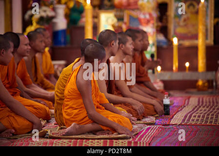 A group of young Buddhist monks sitting on the ground during a ceremony in one of the shrines in their monastery. In Siem Reap, Cambodia. - Stock Photo