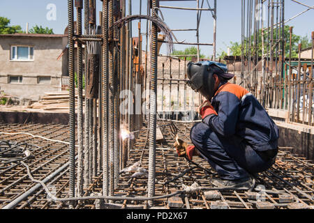 construction worker welding metal rebar for the pouring of foundation. candid, real people - Stock Photo