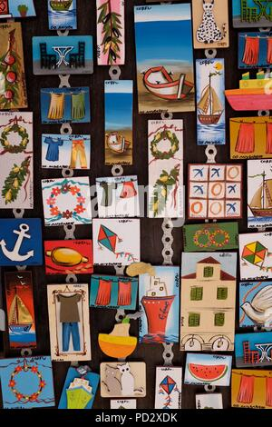 Close up of board of colourful fridge magnets showing local scenes and symbols in souvenir shop, Corfu Island, Greece - Stock Photo