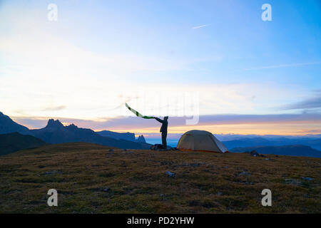 Hiker preparing to camp at sunset, Canazei, Trentino-Alto Adige, Italy - Stock Photo