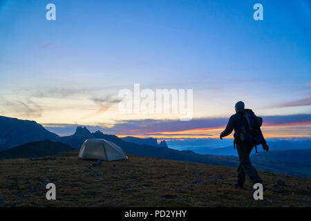 Hiker walking to his tent at sunset, Canazei, Trentino-Alto Adige, Italy - Stock Photo