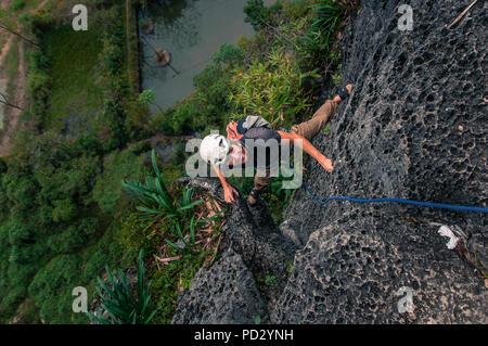 Man rock climbing Guilin Sugarloaf, high angle view, Yangshuo, Guangxi, China - Stock Photo