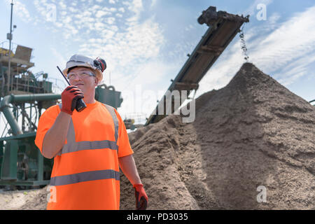 Worker talking on walkie talkie with crusher and concrete screening machine in concrete recycling site - Stock Photo