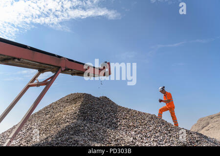Worker checking handful of screened concrete in concrete recycling site - Stock Photo