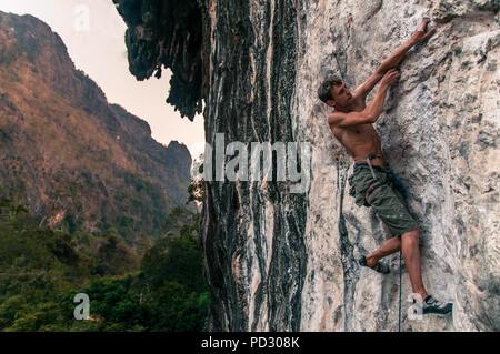 Man sport climbing on limestone, Thakhek, Laos - Stock Photo