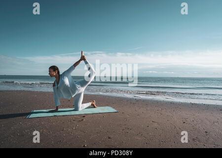 Woman practising yoga on beach - Stock Photo