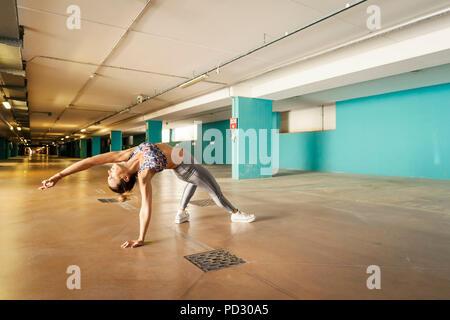 Woman practising yoga in parking lot - Stock Photo