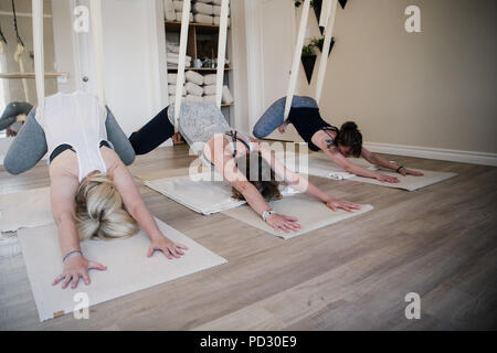 Women doing aerial yoga at retreat - Stock Photo