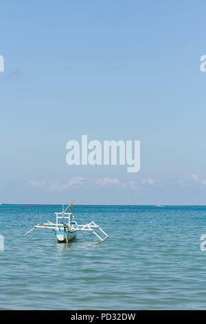 Lombok, Indonesia. A small fishing boat sits anchored in the water off the island of Lombok. - Stock Photo