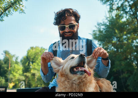 Man and dog having fun, playing, making funny faces while restin - Stock Photo