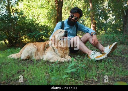 Man with beard and his small yellow dog playing and enjoying sun - Stock Photo