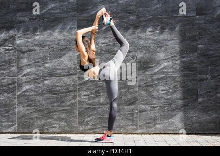 Young fitness woman doing warm-up exercise before running stretching her leg by performing knee to chest stretch on the city street. Sporty athlete pr - Stock Photo