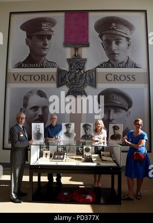 Bovington, UK. 6th August 2018. For the first time in history the four Victoria Crosses awarded to tank crews in the First World War are being brought together at The Tank Museum in Bovington, Dorset  left to right, holding pictures of their respective family mambers are, Ian Robertson with Captain Clement Robertson, Peter Harbinson with Captain Richard Wain, Wendy Shaw with Lt Cecil Sewell and Kitty Morris with Lt Col Richard West Credit: Finnbarr Webster/Alamy Live News - Stock Photo