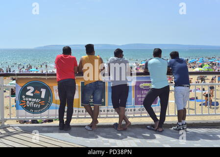 A group of young males looking out over the beach from the pier during summer heatwave 2018, Bournemouth, Dorset, UK - Stock Photo