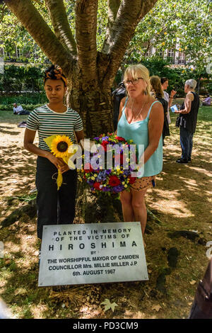 August 6, 2018 - London, UK. 6th August 2018. Women hold a sunflower and the wreath from the Mayor of Camdent in front of the Hiroshima Cherry Tree at the end of the London CND ceremony in memory of the victims, past and present on the 73nd anniversary of the dropping of the atomic bomb on Hiroshima, also remembering those killed and living with the effects of radiation by the second atomic bomb dropped on Nagasaki three days later. The speeches included a reading in English of the statement made earlier in the day at the commemoration in Hiroshima, and an appeal by Rebecca Johnson, on of the - Stock Photo