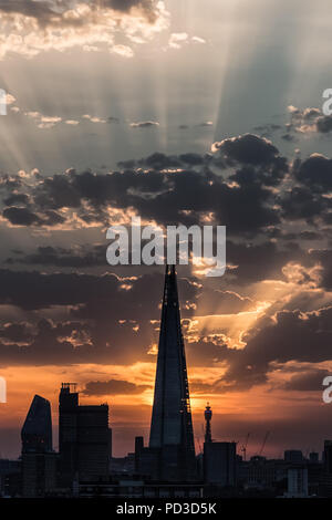 London, UK. 6th August, 2018. UK Weather: Dramatic sun rays over The Shard Skyscraper as the evening sun sets over the city ending another day of heatwave with city temperatures exceeding 30C. Credit: Guy Corbishley/Alamy Live News - Stock Photo