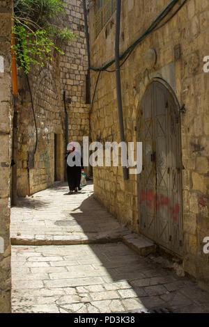11 May 2018 A Muslim woman in traditional Islamic Dress walking a narrow side street off the Via Dolorosa in Jerusalem Israel - Stock Photo