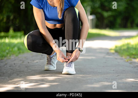 Fitness woman tying laces in running shoes during outdoors workout in the park on a sunny morning - Stock Photo