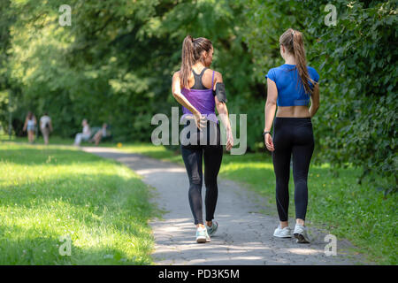 Back view of two attractive fitness girls going on a jogging in a public park on a sunny morning - Stock Photo