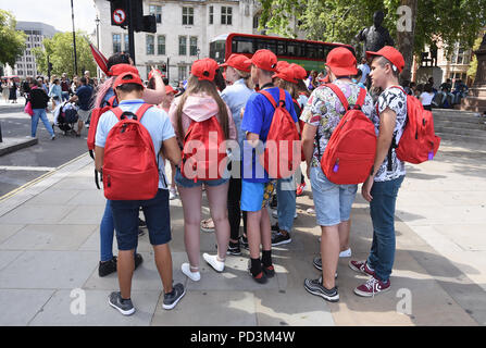 Group of teenage school children on a sightseeing trip,Parliament Square,London.UK - Stock Photo
