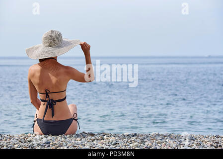 The girl in the hat sits with her back on the pebbles near the sea. - Stock Photo
