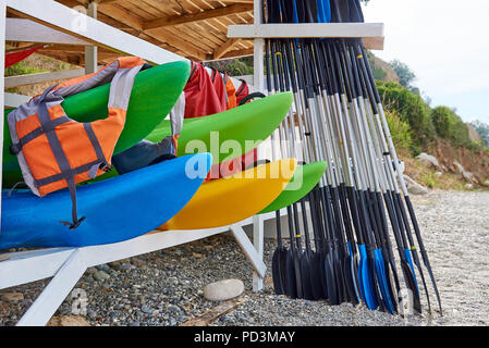 Kayaks, life jackets, oars under a wooden roof on the beach. - Stock Photo