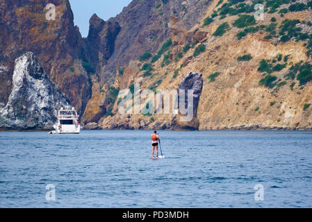 View of the sea, rocks and a floating man but a surfboard near the yacht. - Stock Photo