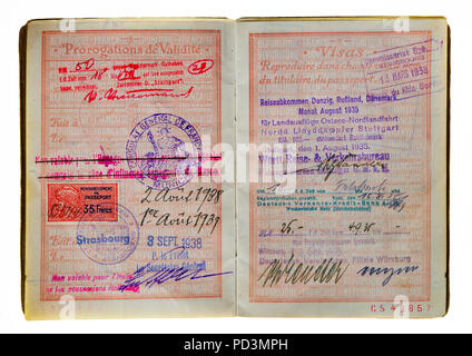 1935's vintage French passport, pages with 1938 renewal date and German travel agency visa stamp mark, - Stock Photo