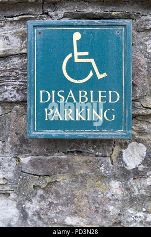 Disabled Parking sign with yellow text and man person in wheelchair symbol with green background on an old stone wall - Stock Photo