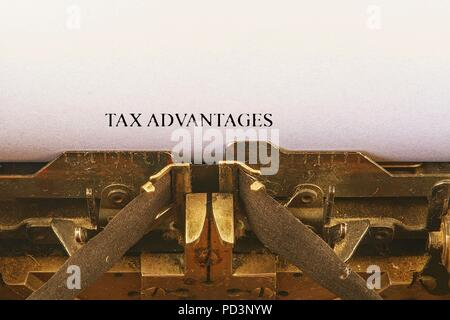 Closeup on vintage typewriter. Front focus on letters making TAX ADVANTAGES text. Business concept image with retro office tool - Stock Photo