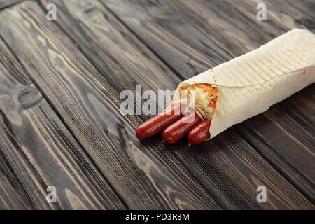 hunting sausages in pita bread on a dark wooden background - Stock Photo