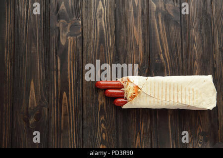 smoked sausage in pita bread on a dark wooden background.photo w - Stock Photo