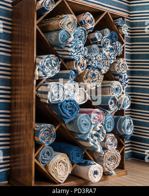 Fabric rolled up in shelf - Stock Photo