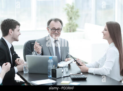 Manager discussing work issues with his assistants behind a Desk - Stock Photo