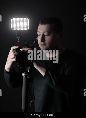 professional photographer with camera on tripod.isolated on black background - Stock Photo