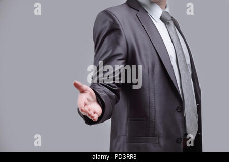 close up. the businessman extends his hand for greeting .isolated on grey background - Stock Photo