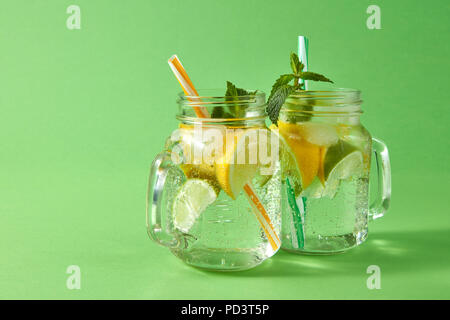 Cold natural lemonade with bubbles of air from natural tropical ingredients - citrus fruits slices, ice, leaf of mint, water. Two glass jars with plastic straws on green. - Stock Photo