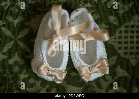 Little baby girl booties in white with beige ribbons, view from above against an ornate cushion background, adorable footwear reserved for Christening - Stock Photo
