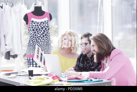 designer group works on a laptop in a creative office - Stock Photo