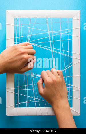 Mental health concept. Women's hands try to break the fetters on blue background - Stock Photo