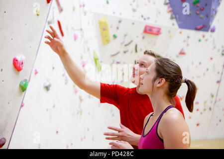 Photo of young female athlete and man on wall background for rock climbing - Stock Photo